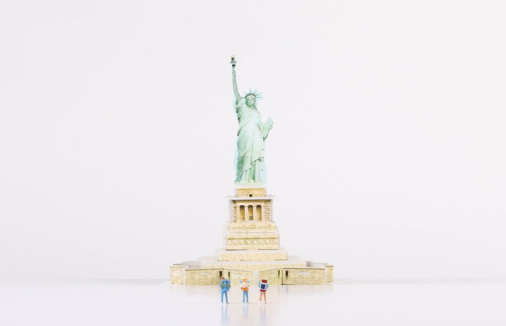 Miniature travelers stading in front of Statue of Liberty