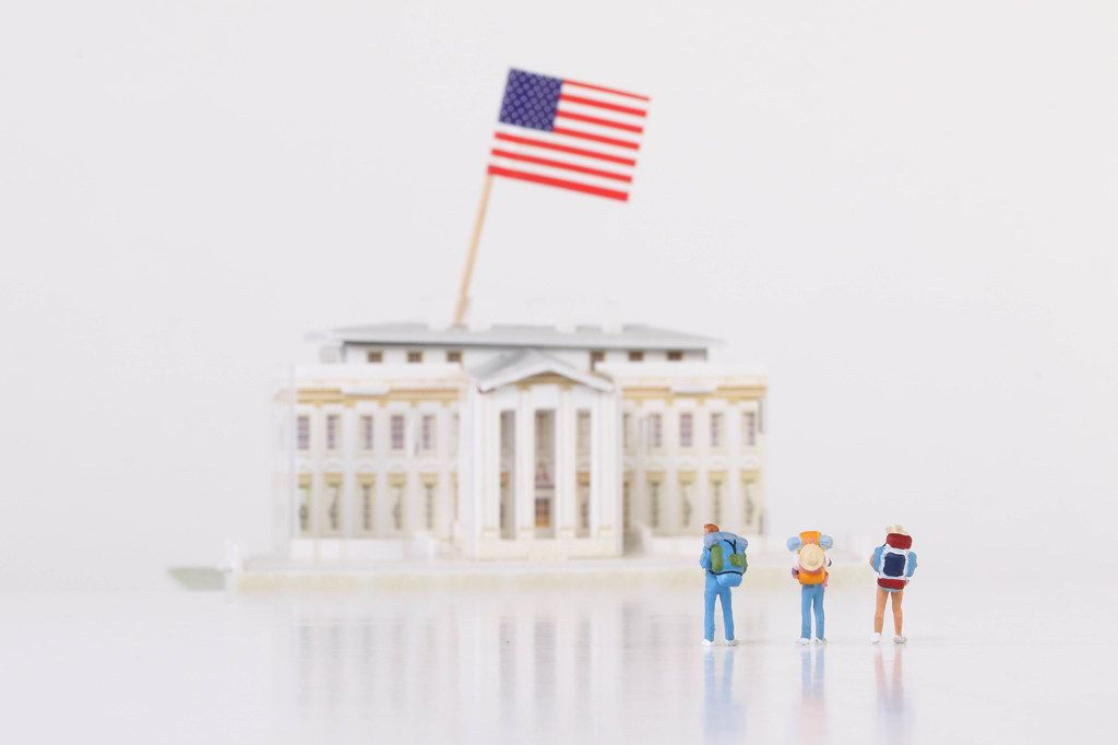 Miniature travelers stading in front of the White House on white background