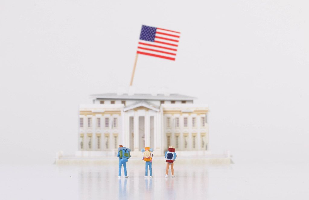 Miniature travelers stading in front of the White House with USA flag