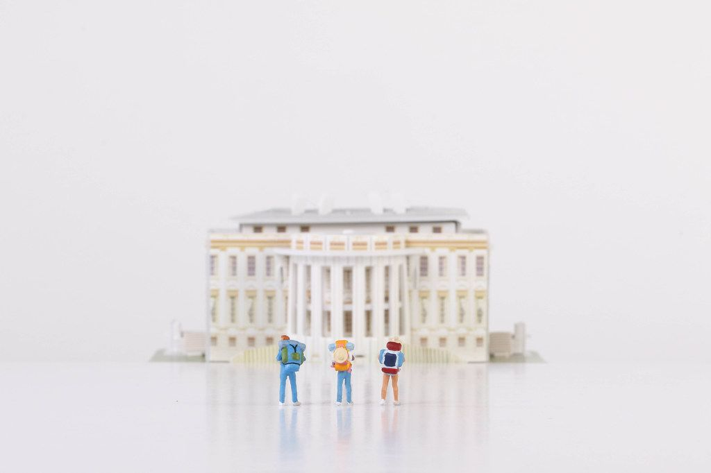 Miniature travelers stading in front of the White House