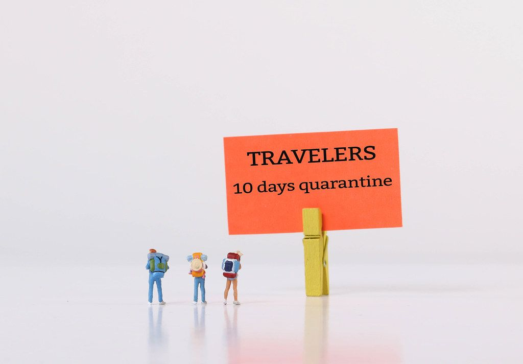 Miniature travelers standing in front of sign for 10 days quarantine