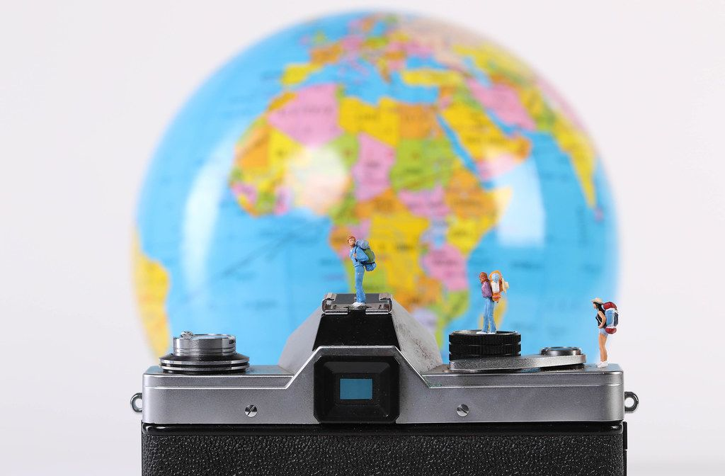 Miniature travelers standing on camera with globe in the background
