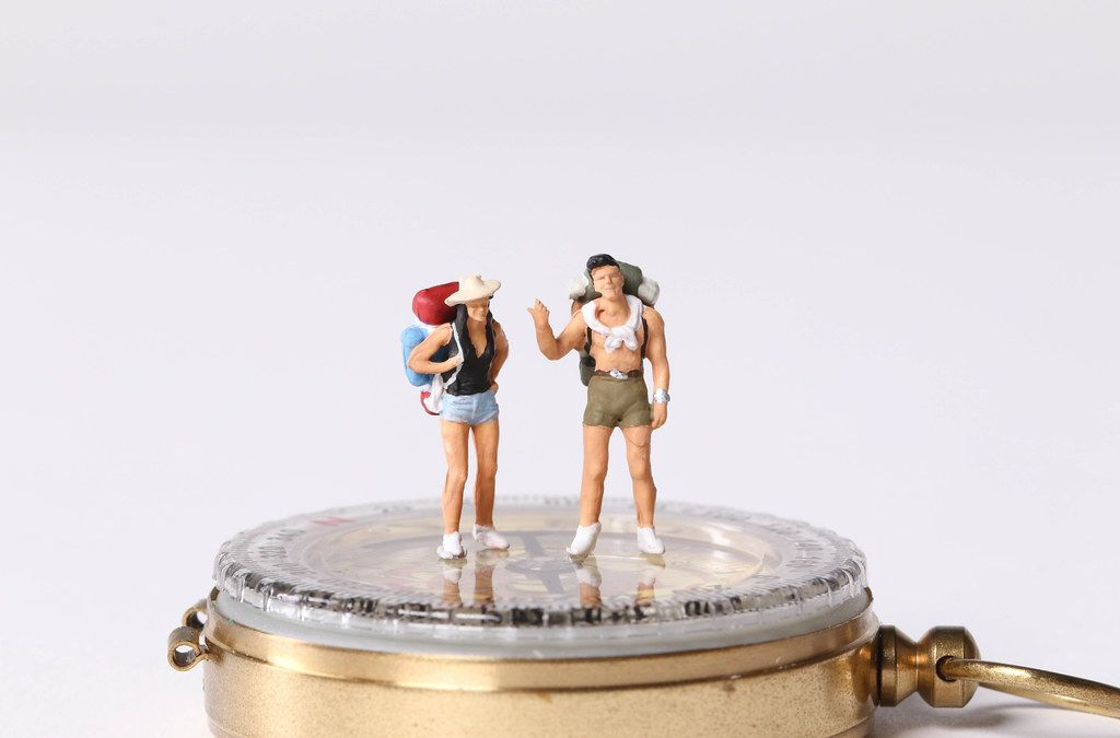 Miniature travelers standing on compas