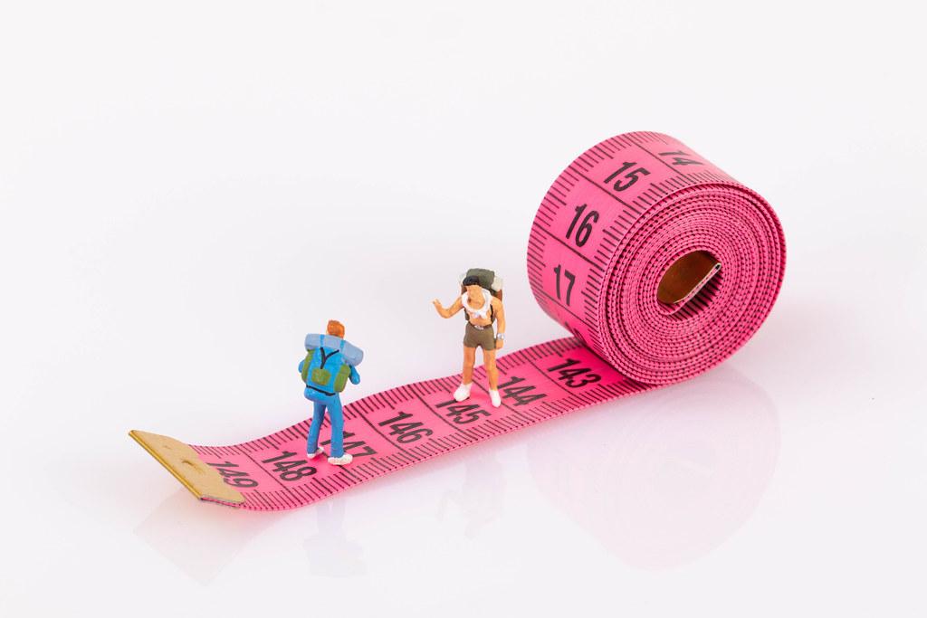 Miniature travelers standing on measure tape