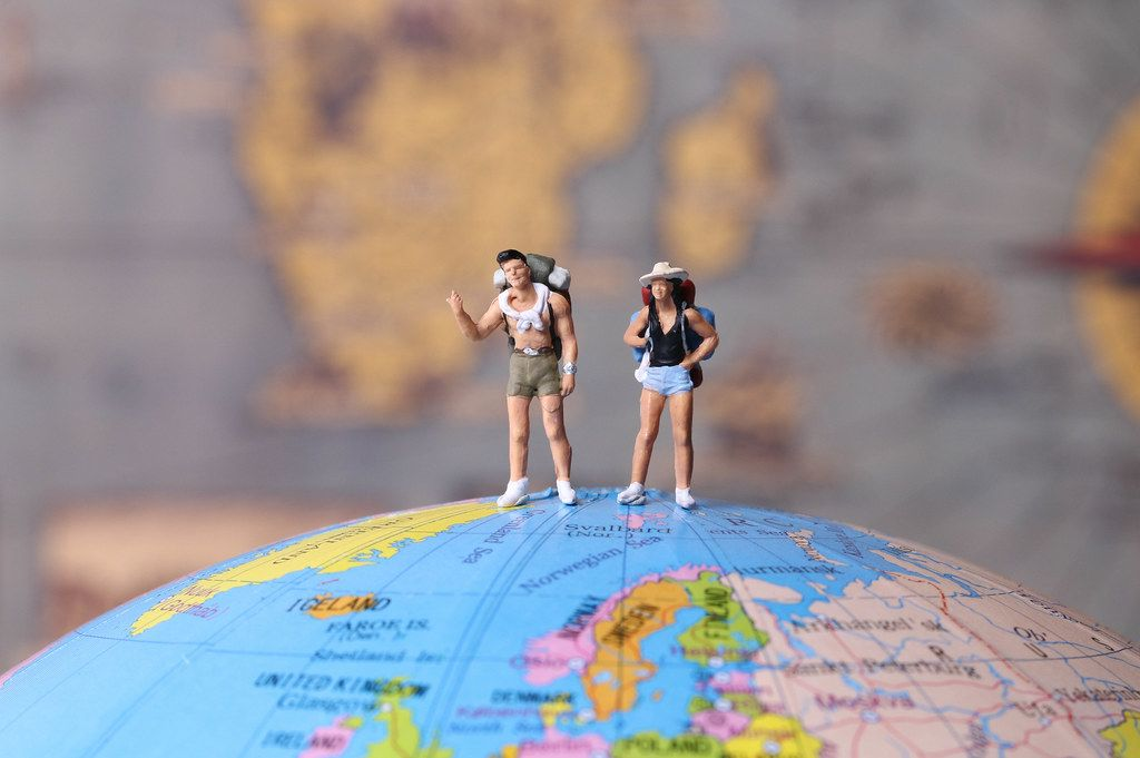 Miniature travelers standing on the globe with map in the background