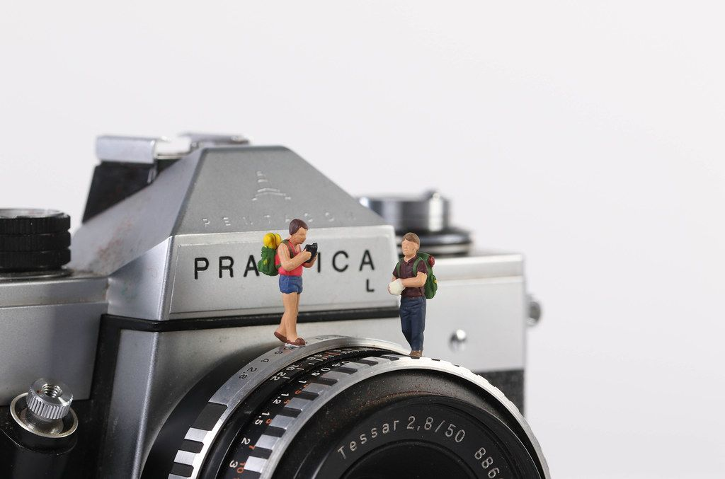 Miniature travelers standing on vintage camera