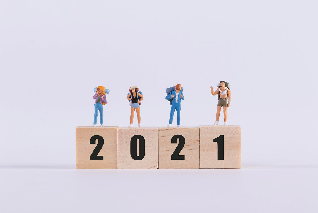 Miniature travelers standing on wooden cubes with 2021 text