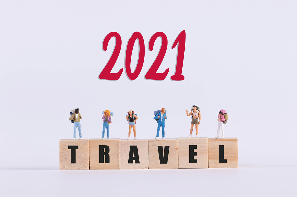 Miniature travelers standing on wooden cubes with Travel text and red 2021 text