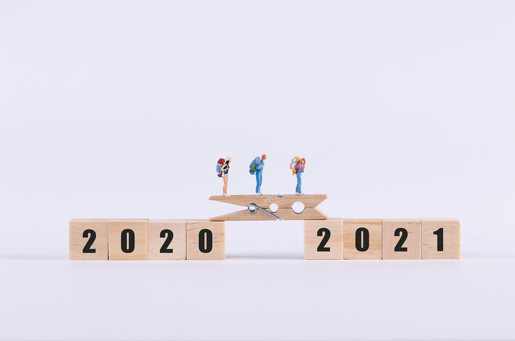 Miniature travelers walking on wooden bridge between 2020 and 2021 text