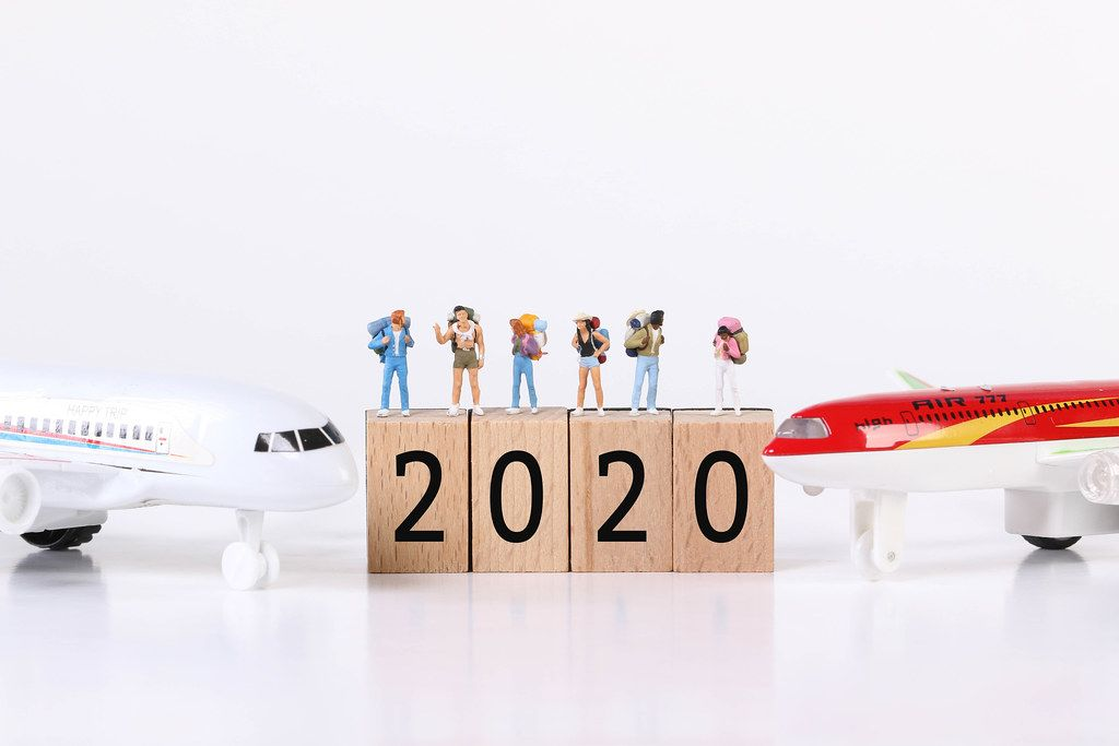 Miniature travelers with toy airplanes and 2020 text