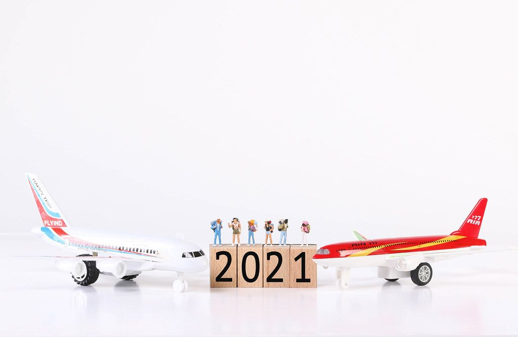 Miniature travelers with toy airplanes and 2021 text