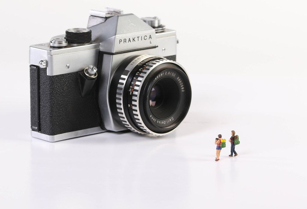 Miniature travelers with vintage camera on white background