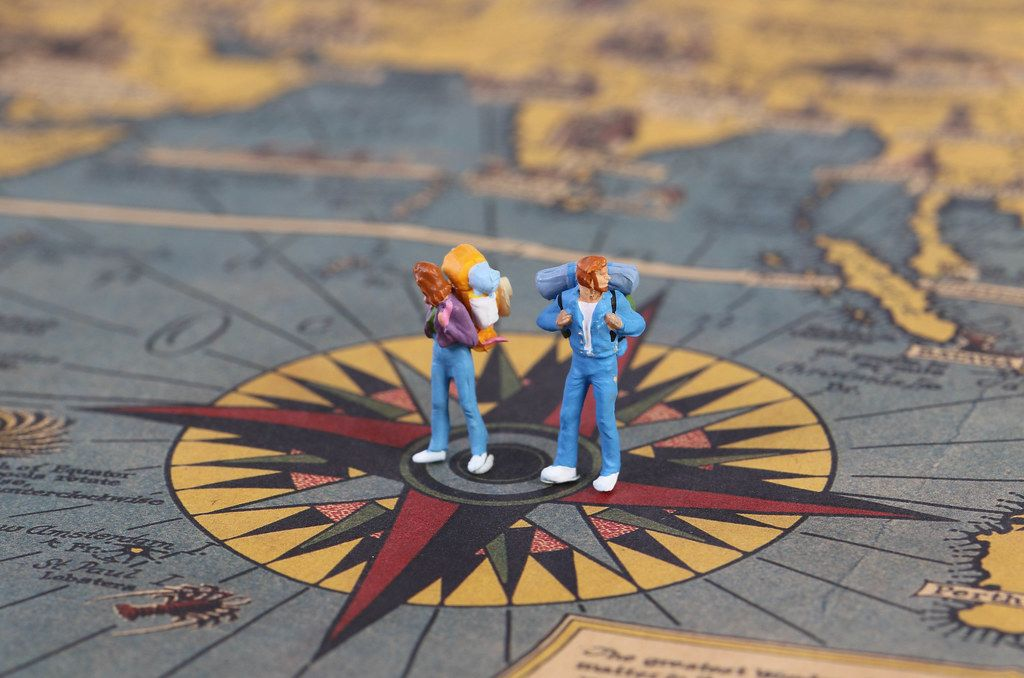 Miniature travlers standing on the compas on map