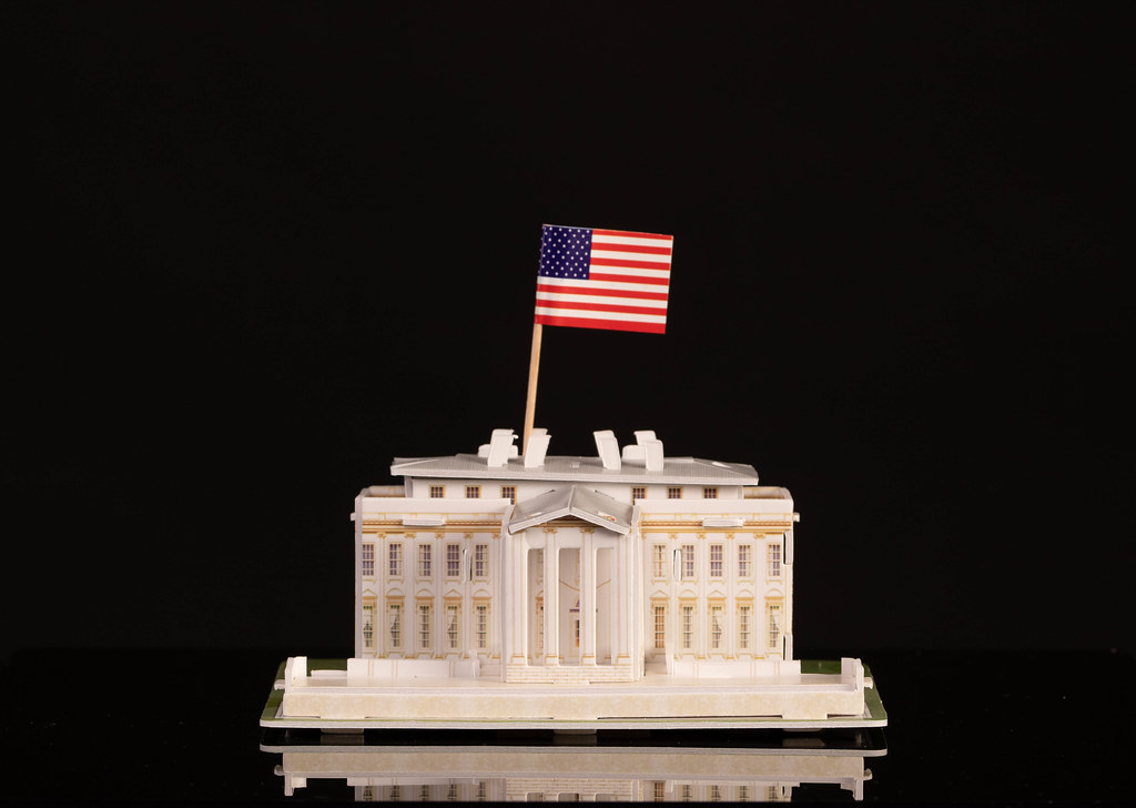 Miniature White House with American flag on black background