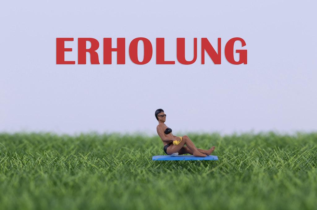 Miniature women relaxing on green grass eith Erholung text