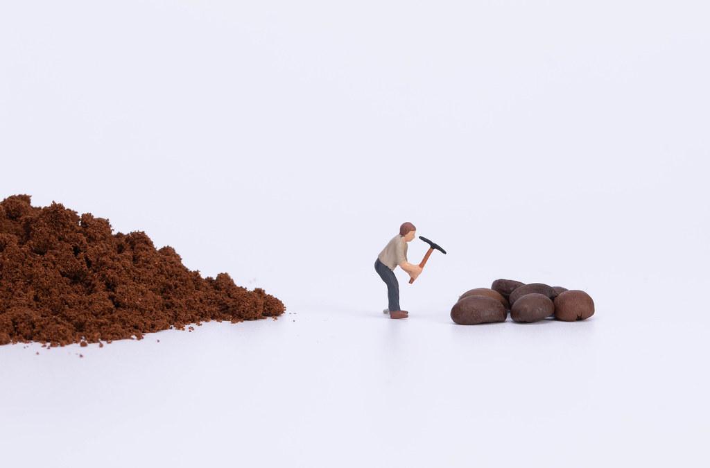 Miniature worker grinding coffee beans