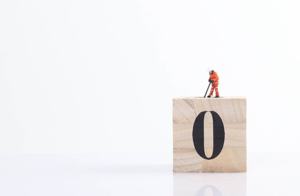 Miniature worker on wooden cube with big zero