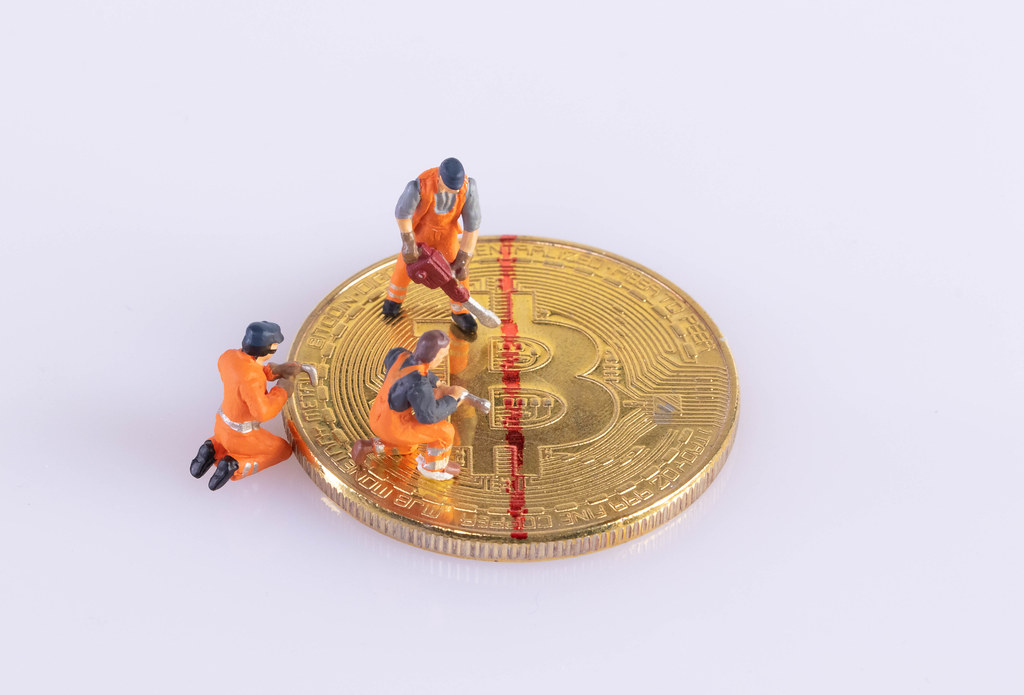 Miniature workers cutting Bitcoin. Halving concept