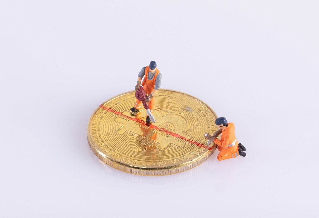 Miniature workers cutting Bitcoin