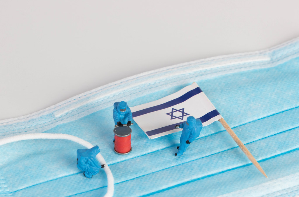 Miniature workers in protective clothes on a medical mask with flag of Israel