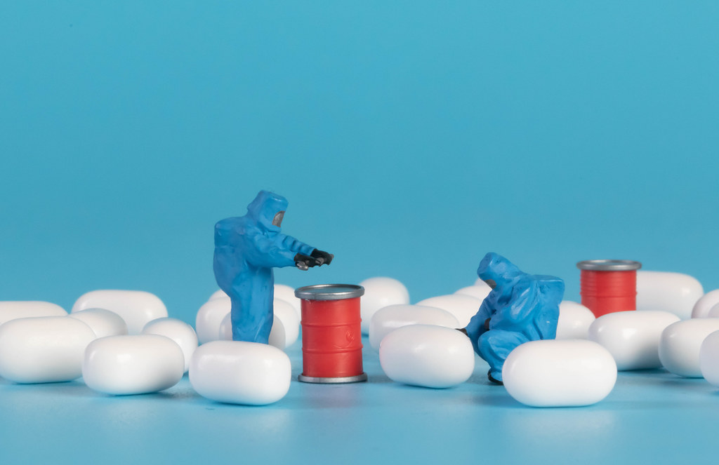 Miniature workers in protective clothes will pills on blue background
