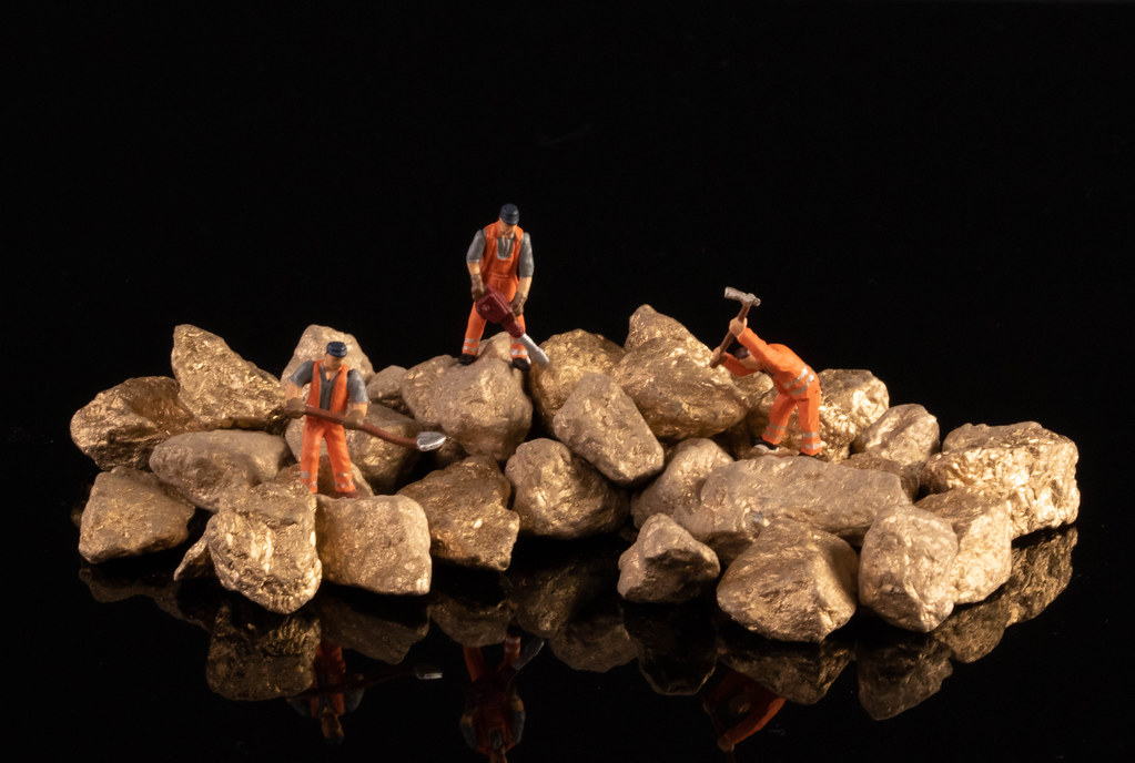 Miniature workers with gold nuggets on black background