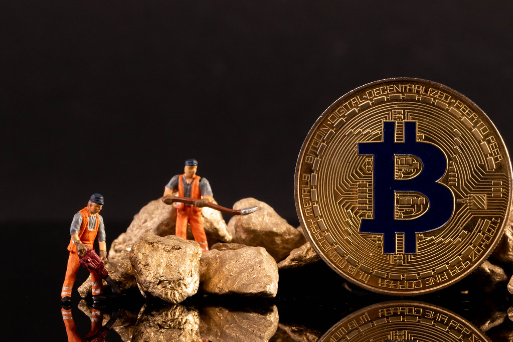Miniature workers with golden Bitcoin and gold nuggets on black background