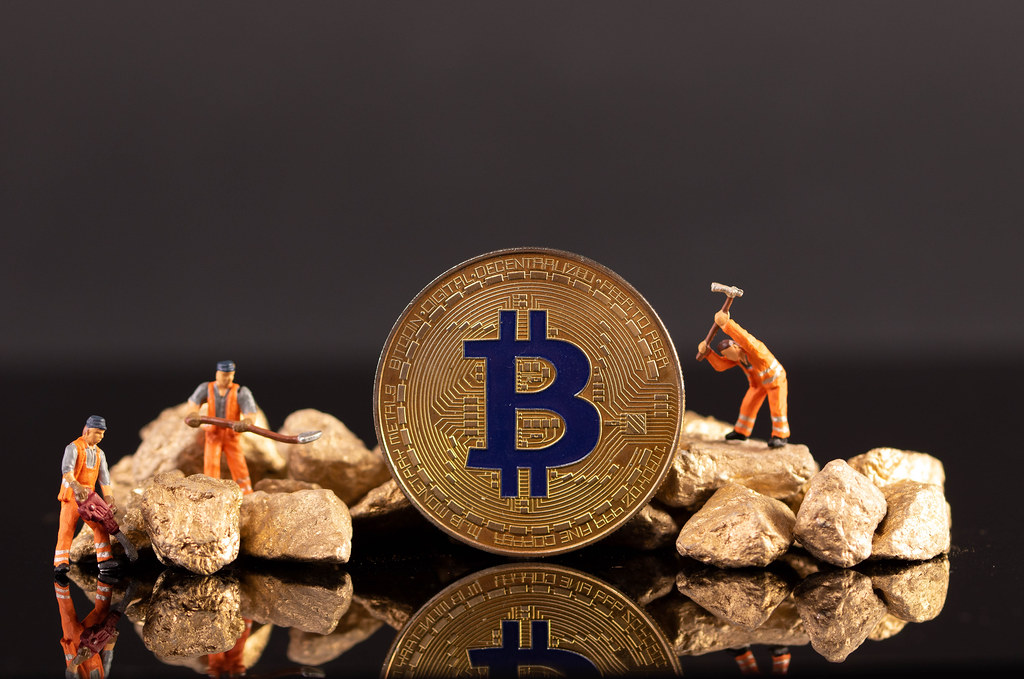 Miniature workers with golden Bitcoin and gold nuggets