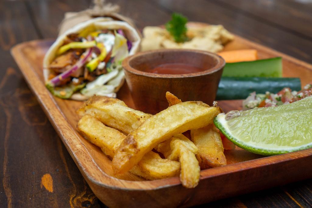 Mittagessen Set auf einem Holzbrett bestehend aus Döner Dürum Wrap mit Hähnchenfleisch, Pommes Frites, Hummus, Quinoa Salat und Gemüse Nahaufnahme