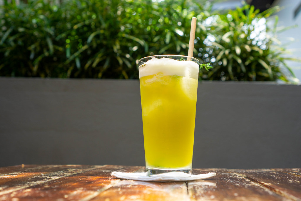 Mixed Fruit Juice with Passion Fruit, Pineapple and Yuzu in a Glass with Paper Straw and Rosemary on a Fabric Saucer with Plants in the Background