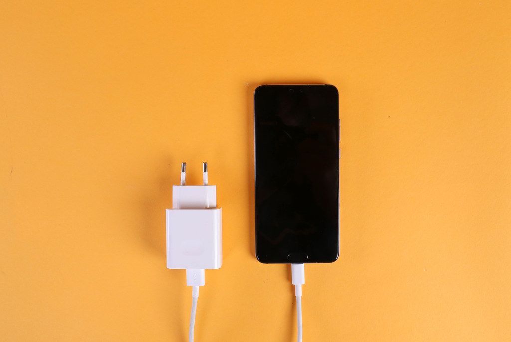 Mobile phone and charger cable on orange background