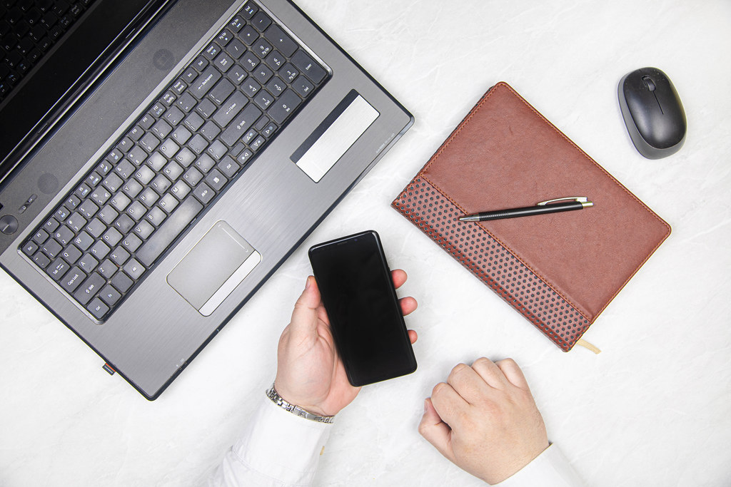 Mobile phone in the hand of a businessman in front of a laptop