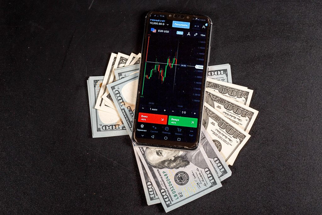 Mobile phone with a trader program on the screen with cash on a black background