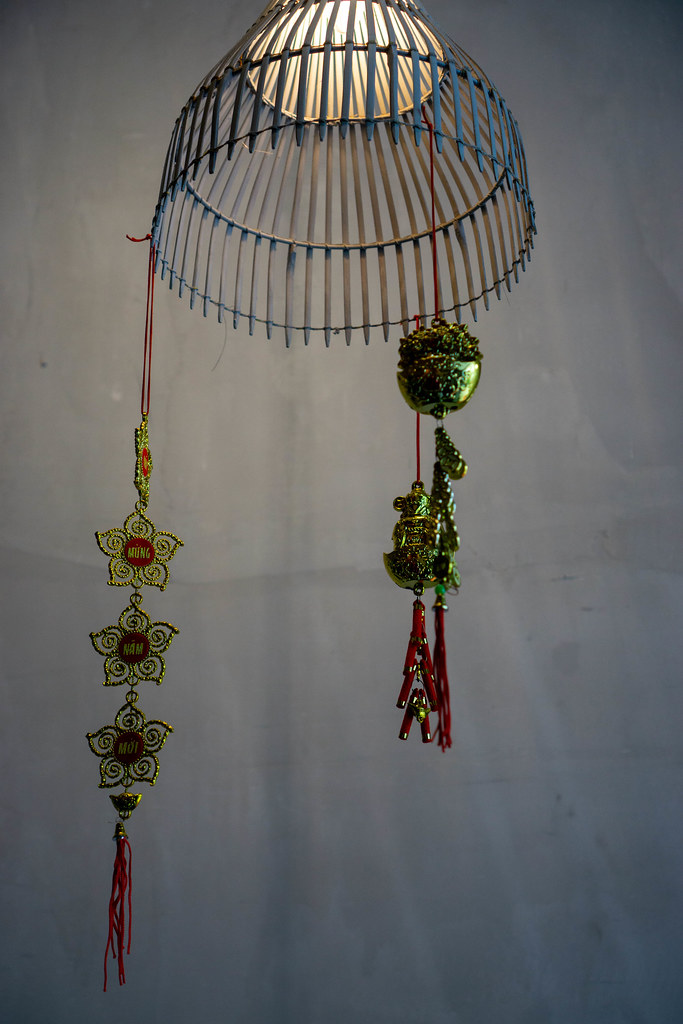 Modern Ceiling Lamp with Bright Light Bulb with Hanging Red Ornaments as Decoration in a Restaurant