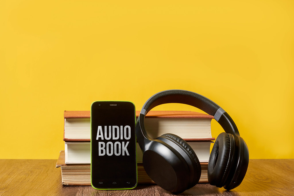 Modern wireless headphones with hardcover books and smartphone against the yellow colored background