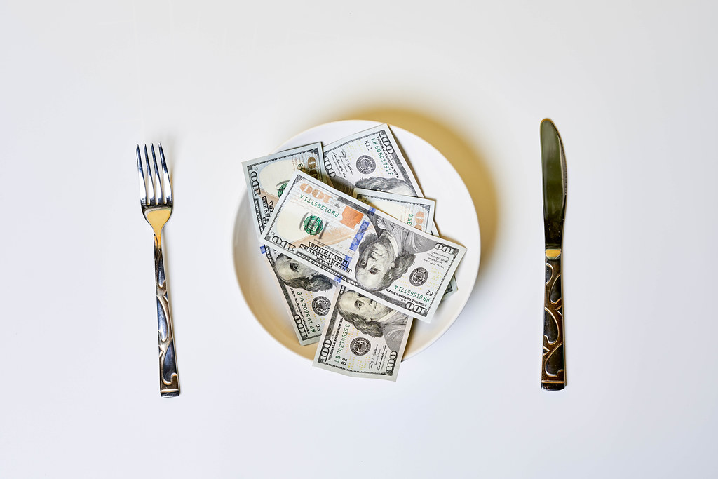 Money on the plate with fork and knife - greedy corruption or bribe idea