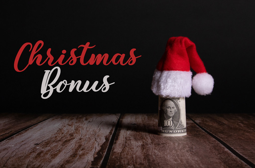 Money roll with Christmas hat and Christmas Bonus text on black background