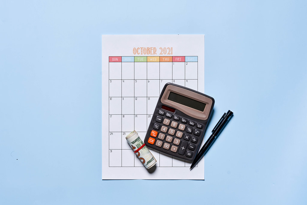 Monthly budget planning - money and calculator on the october monthly calendar