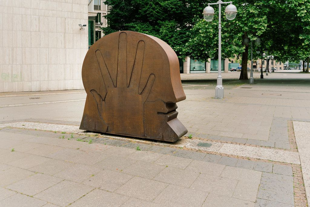 Monument with head and palm in the street of Hannover, Germany