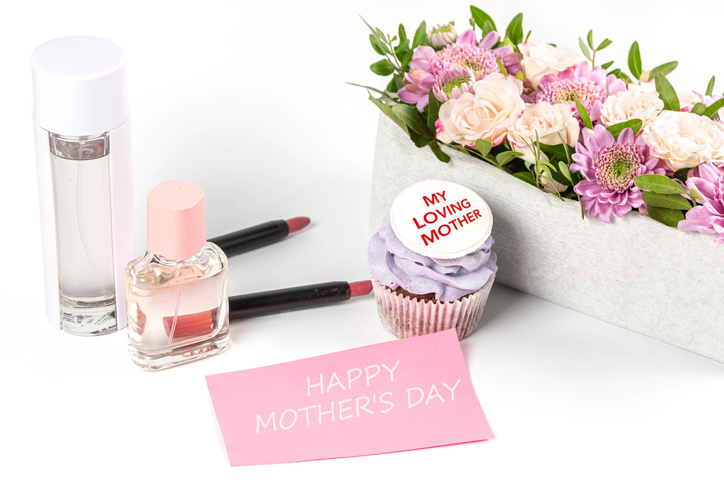 Mothers day greeting background with perfumes, lipsticks, flowers and cupcake