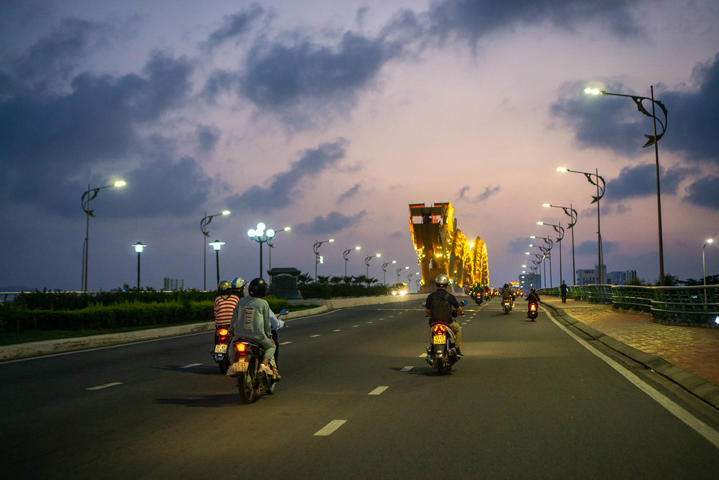 Motorbikes driving towards the Dragon Head of the iconic Dragon Bridge with Colorful Sky in the Evening in Da Nang, Vietnam