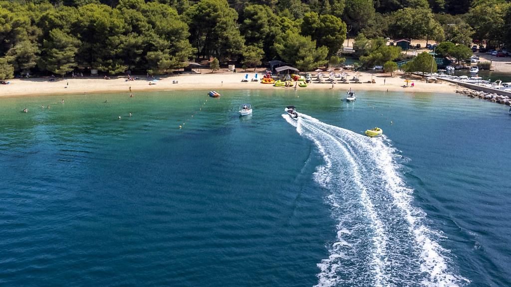 Motorboote und Aquadonuts vor dem Strand Chrysi Ammos auf Skiathos, Griechenland