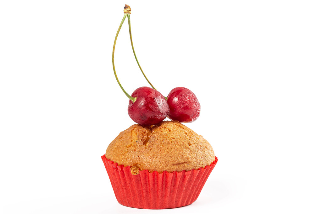 Muffins with cream filling and ripe cherries