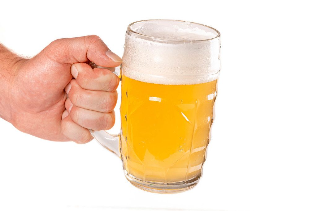 Mug of unfiltered light beer with foam in a man