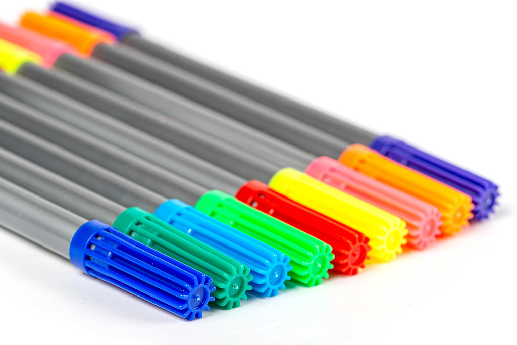 Multi-colored felt-tip pens on a white background, close-up