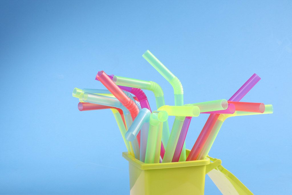 Multicoloured plastic drinking straws on blue background