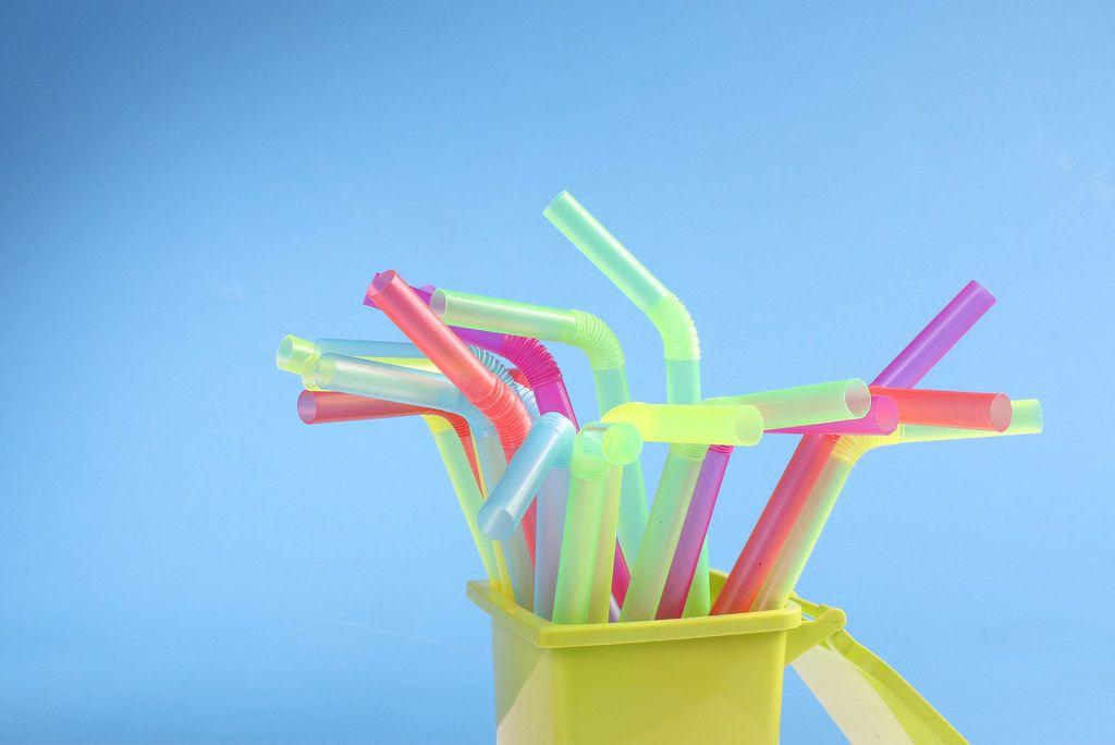 Multicoloured plastic drinking straws on blue background