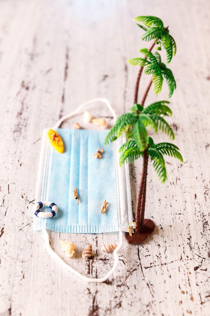 Mund-Nasen-Schutz mit Miniaturfiguren und Palmen. Urlaub am Strand trotz Corona im Sommer 2020