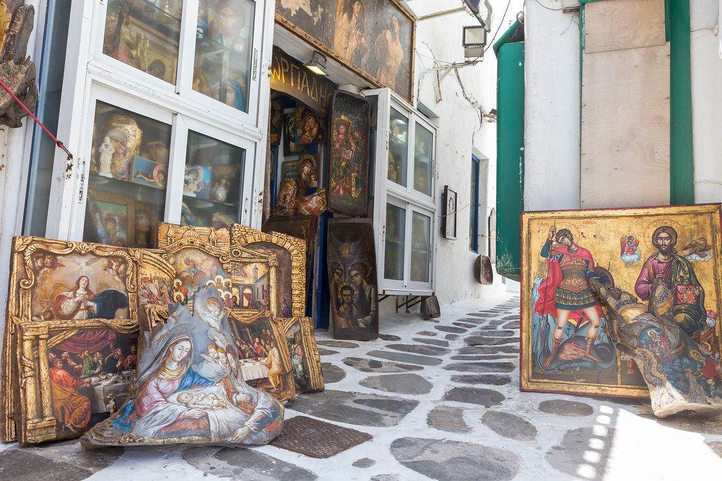 Mykonos, Griechenland: Kunstladen, der christliche Gemälde in einer Gasse verkauft