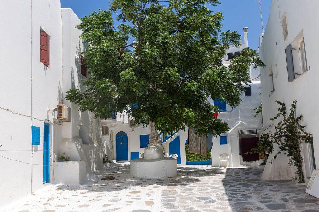 Mykonos: kleiner Platz mit Baum in der Mitte und weißen Häusern mit blauen Türen und Fenstern